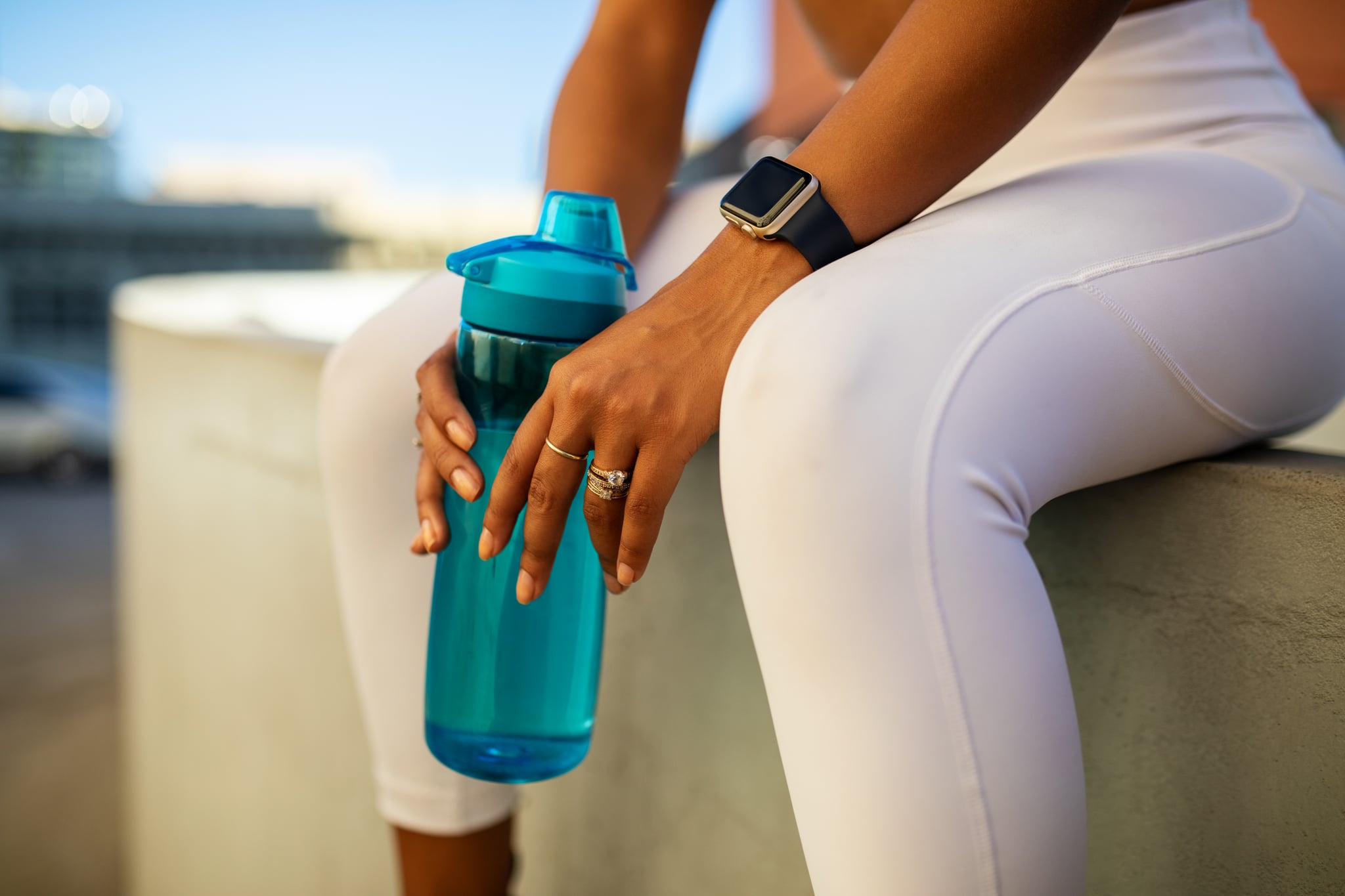Mid section of tired woman holding water bottle. Female in sports wear sitting on wall after workout session in city.